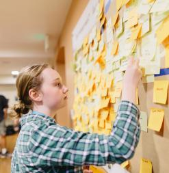 A participant places a post-it note on a wall of ideas.